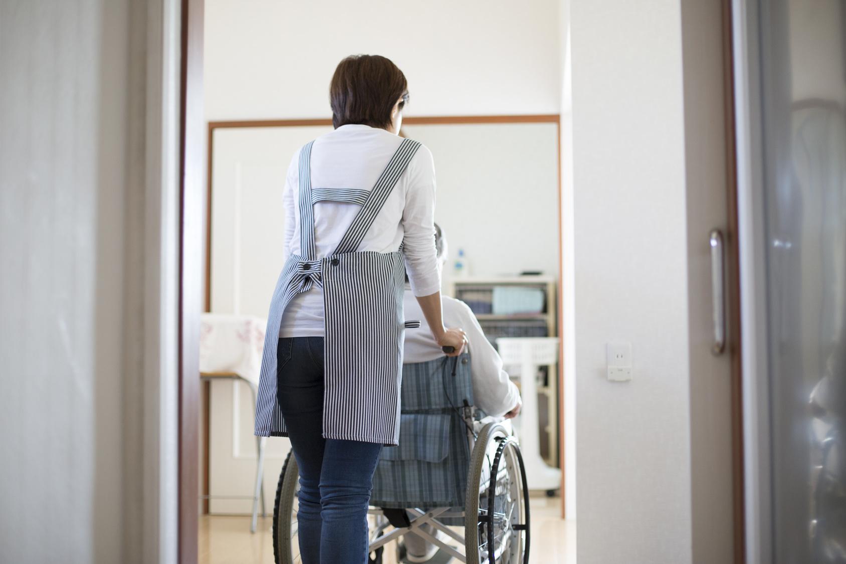 在宅介護、自宅にの廊下でヘルパーと老人の後姿